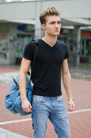Attractive young man standing in city environment, with rucksack on one shoulder Stock Photo - 24520683