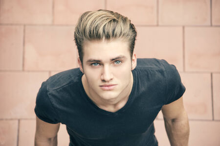blonde blue eyes: Attractive blond young man shot from above, looking up towards camera Stock Photo
