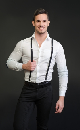 Elegant young man with white shirt and suspenders, on dark background, smiling photo