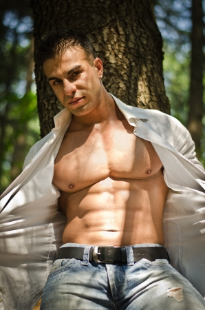 Muscular man with open shirt in jeans outdoors under trees looking down photo