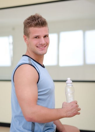 Attractive, nice male athlete holding plastic bottle of water, smiling and looking at camera photo