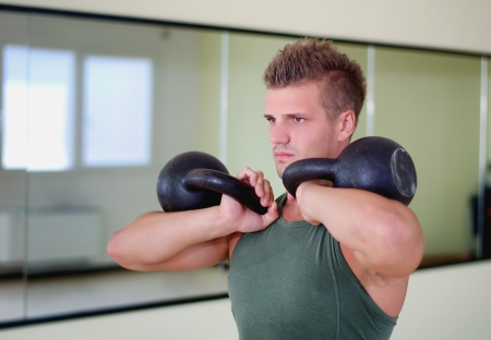 Attractive young athletic man exercising in gym, working out using kettlebells photo