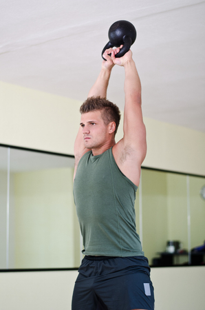 Attractive young athletic man exercising in gym, working out using kettlebell photo