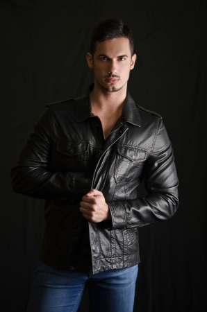 Portrait of attractive young man with leather jacket and jeans on dark background photo