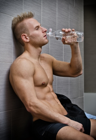 look after: Blond shirtless young male athlete drinking water after workout, sitting against wall