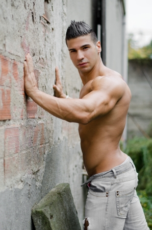Muscular young latino man shirtless in jeans leaning against concrete wall, looking at camera photo