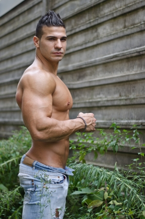 Muscular young latino man shirtless in jeans outdoors looking at camera Stock Photo