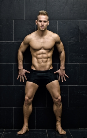 bodybuilder: Sexy, muscular young man standing in underwear against dark wall, full body figure, looking at camera
