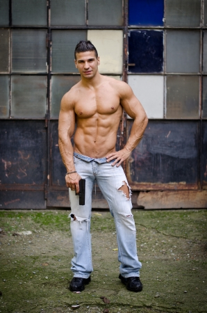 Shirtless, muscular latino young man holding gun, pointing it to the ground Stock Photo