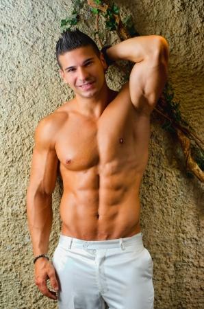 Gespierde jonge latino man shirtless in witte broek leunend op de muur, glimlachen en kijken naar camera