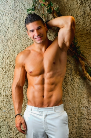 Muscular young latino man shirtless in white pants leaning on wall, smiling and looking at camera Stock Photo