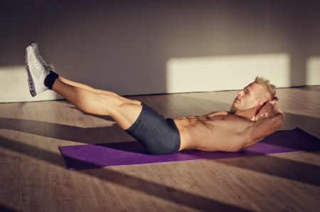 Attractive blond young man shirtless in gym working out, doing exercises for abs photo