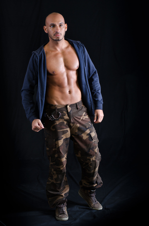 Bald young man standing wearing sweatshirt on chest and military pants photo