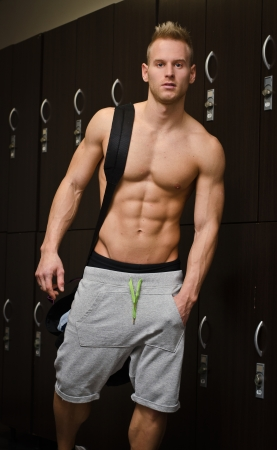 locker room: Shirtless muscular young male athlete in gym dressing room, with backpack on shoulder