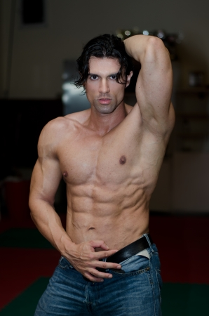 Attractive shirtless male bodybuilder in jeans indoors, showing muscular torso and ripped abs