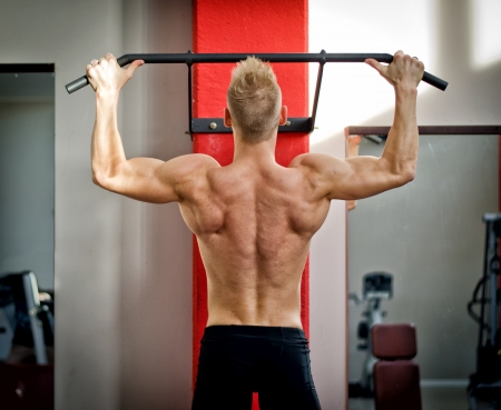 pullups: Blond, attractive young man hanging from gym equipment, seen from the back