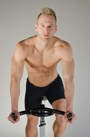 Attractive young man exercising in gym: spinning on stationary bike photo