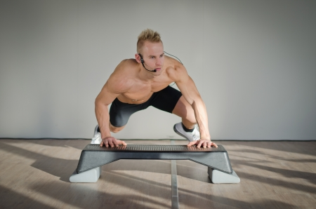 Young aerobics male coach shirtless leaning on step teaching class photo
