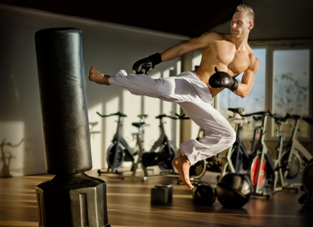 Shirtless handsome muscular young man in gym doing flying kick, wearing boxing gloves