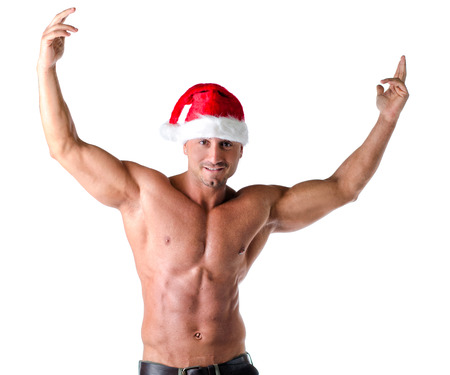 Christmas season: muscular bodybuilder shirtless wearing Santa Claus red hat, isolated on white photo