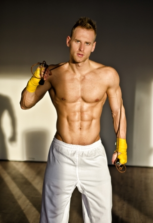 Shirtless muscular young man standing with jumping rope in gym, looking at camera photo
