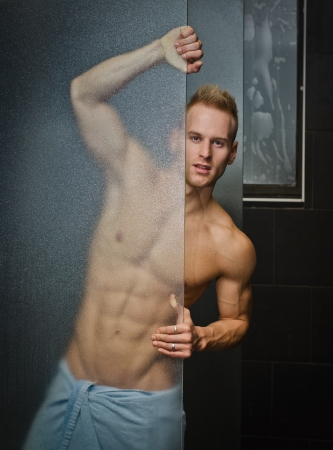 man shower: Handsome young man shirtless behind shower glass, with towel around waist