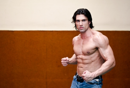 Attractive shirtless muscular man in jeans indoors with ripped torso, abs, pecs and arms photo