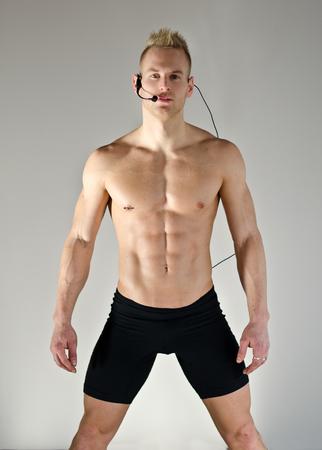 Young aerobics male coach shirtless standing, teaching class photo