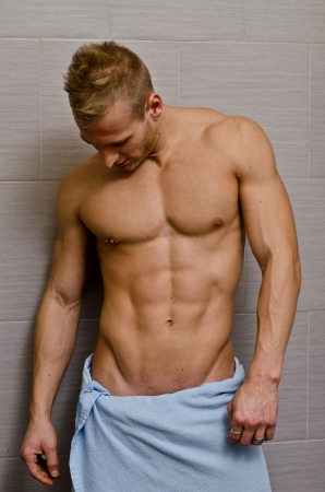 Handsome semi-naked muscular young man in bathroom with towel looking at his torso photo