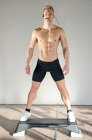 Young aerobics male coach shirtless standing on step teaching class photo