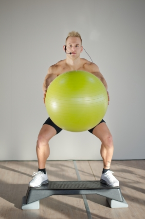 Young aerobics male coach shirtless standing on step teaching class holding big fitness ball photo