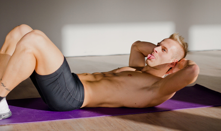 Shirtless, muscular young man sticking tongue out while training abs photo