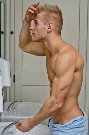 Shirtless, muscular young man, towel around waist, looking at his hair in bathroom mirror photo
