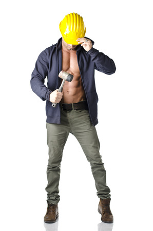 Attractive, muscular construction worker with open sweatshirt and hammer, wearing yellow hard hat, isolated on white photo