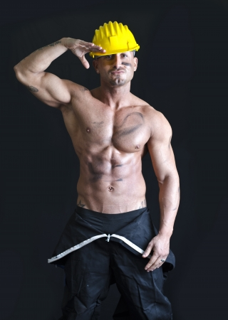 Shirtless muscular construction worker wearing coverall and hardhat with friendly expression photo