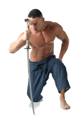 Muscular man kneeling on the floor shirtless, with japanese sword in his hand, isolated on white photo
