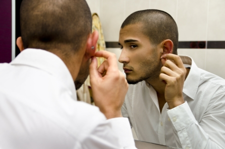 Handsome young man touching and examining his ear piercings Imagens