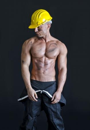 Shirtless muscular construction worker wearing coverall and hardhat looking to a side photo