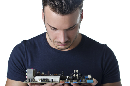 Confused, puzzled computer technician, a handsome young man, looking at motherboard photo