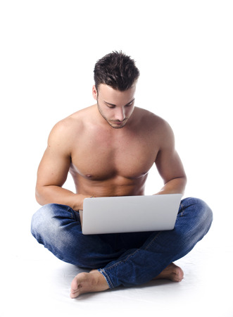 Muscular, shirtless young man on the floor using laptop computer, isolated on white background photo