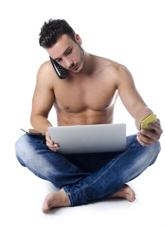 Shirtless muscular young man overwhelmed by technology, using laptop computer, PC tablet, phones photo