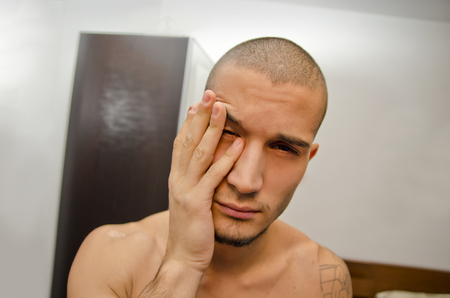 Attractive young man in bedroom just woken up, still tired