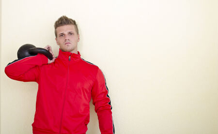 tracksuit: Serious young man (personal trainer or athlete) in tracksuit with kettlebell. Large copyspace