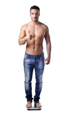signos de pesos: Muscular joven que se pesa en escala, haciendo el signo de OK con el pulgar arriba Foto de archivo