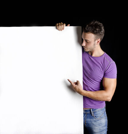 Handsome young man with large blank display or board, on black background photo