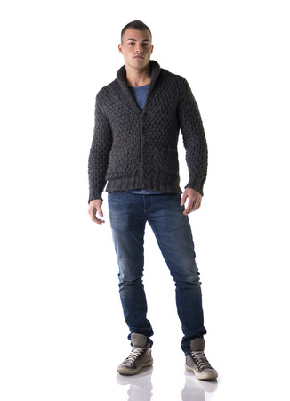 Full body shot of attractive young man with wool sweater and jeans, isolated on white background photo