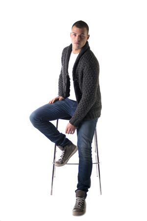 Attractive young man sitting on stool with wool sweater and jeans, isolated on white background