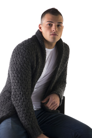 Attractive young man sitting with wool sweater and jeans, isolated on white background photo