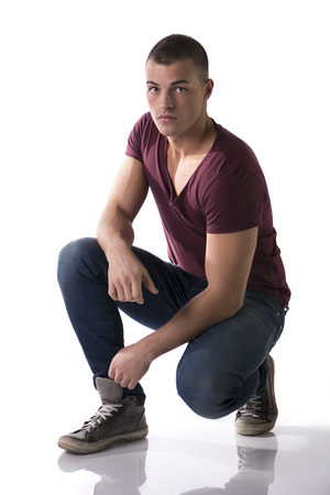 Handsome young man with t-shirt and jeans crouching on floor, isolated on white photo