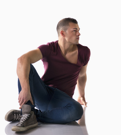 Full body shot of handsome young man with t-shirt and jeans sitting on the floor, isolated on white photo